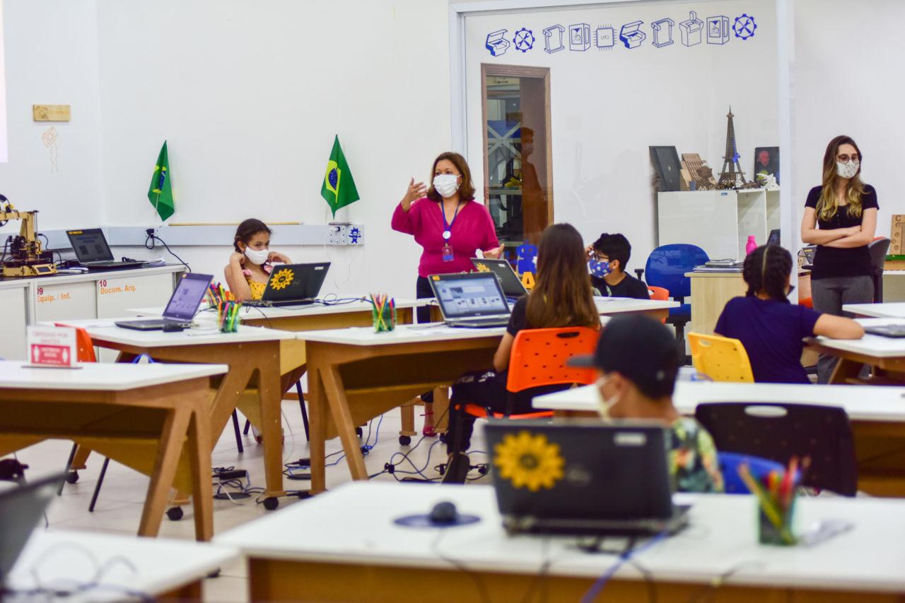 imagem mostra o Fab Lab, com mesas e computadores, crianças estão em frente ao computador.