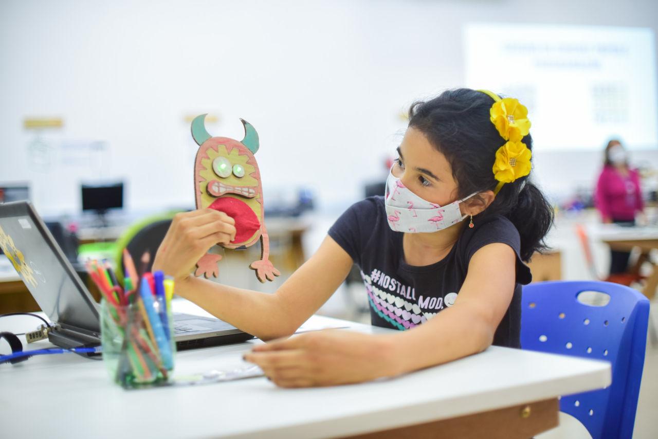 """garota morena, com tiara amarela com duas flores também amareladas nos cabelos, segura protótipo na mão, feito de papelão, colorido, que parece um """"monstrinho"""", com os olhos de led, estão acesos."""