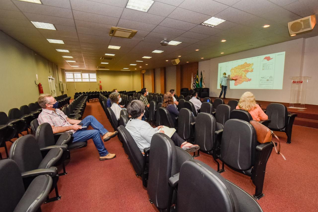Imagem mostra auditório com algumas pessoas sentadas em cadeiras, seguindo distanciamento social. À frente, está um homem fazendo apresentação. Na projeção há um mapa com cores laranja, amarela e vermelho.