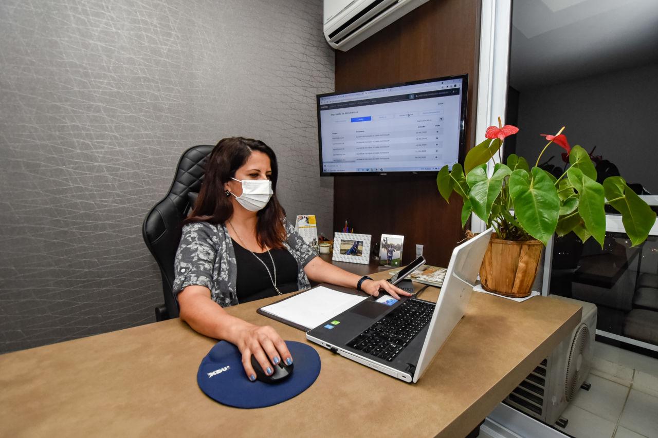 Mulher morena está sentada em atrás de mesa de madeira, onde estão apoiados vaso com flores vermelha e folhas verdes, computador, papéis. Ela mexe no computador. ao seu lado há um painel de madeira, onde está afixada uma televisão