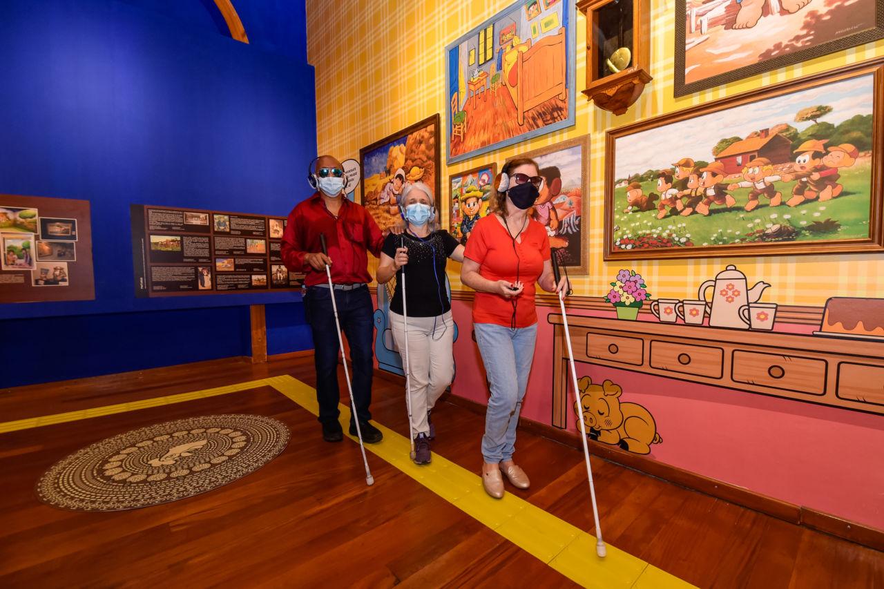 Um homem e duas mulheres usando máscaras percorrem exposição usando bengala de cego