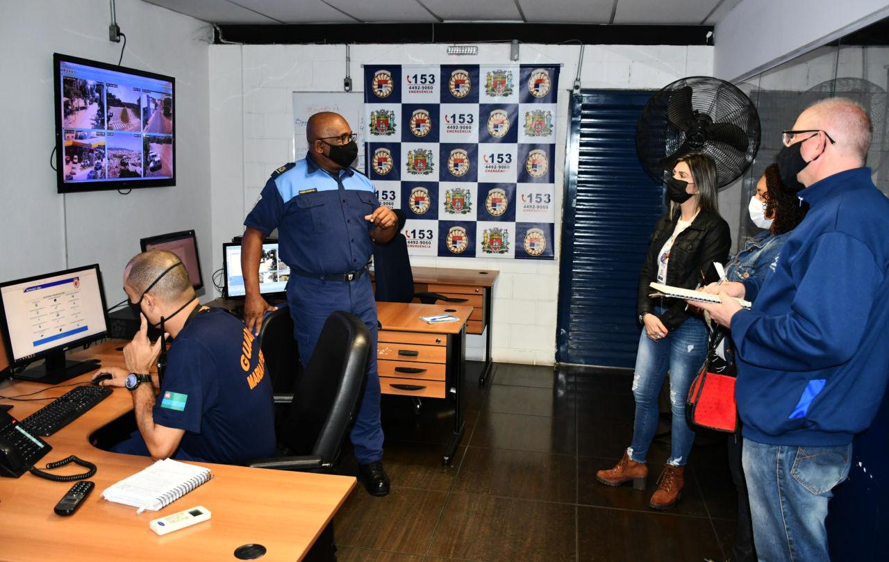 Duas mulheres e um homem usando máscaras, à direita do vídeo, conversam com dois guardas com uniformes, no canto esquerdo da foto, com computadores sobre mesas, um televisor com imagens de câmeras de monitoramento e placa com brasões estendida sobre a parede do fundo