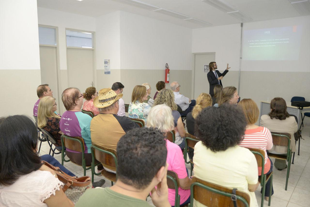 Plateia assistindo a apresentação, com palestrante em pé, apontando para slide projetado na parede