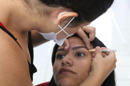 Aluna tira a sobrancelha de uma mulher, durante curso