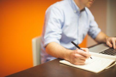 Homem sentado em uma mesa, escrevendo em folha de papel